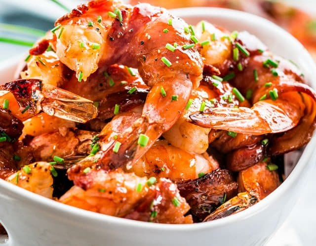 a bowl full of maple bbq glazed bacon wrapped shrimp