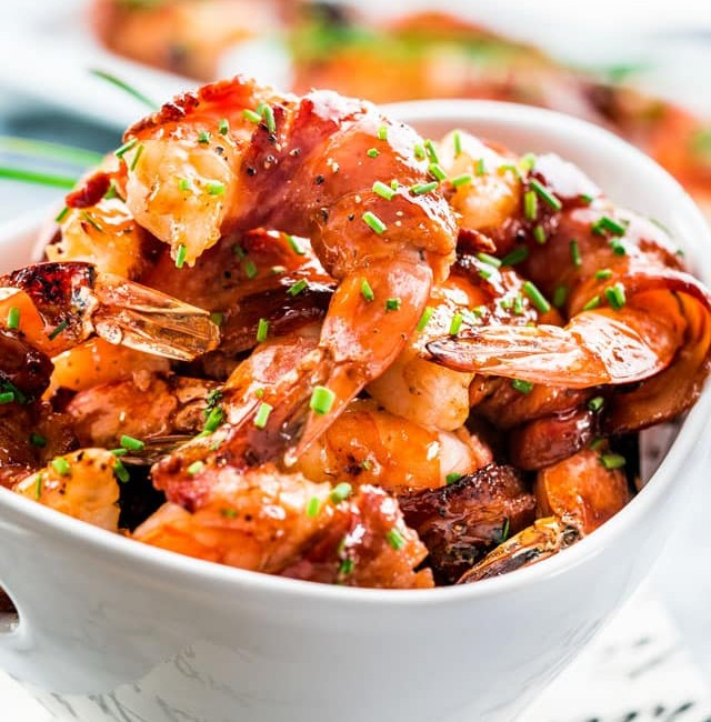 a bowl full of maple bbq glazed bacon wrapped shrimp