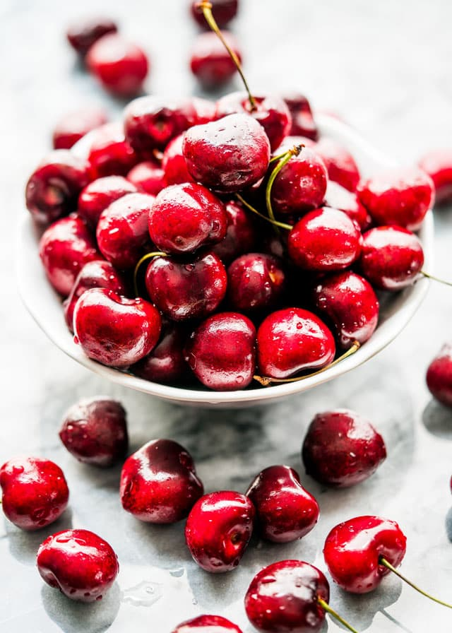 a bowl full of fresh red cherries