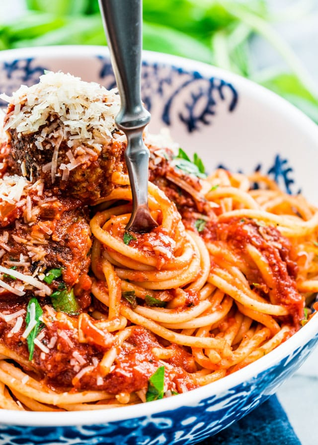 a fork twirling spaghetti with meatballs, parmesan, and tomato sauce