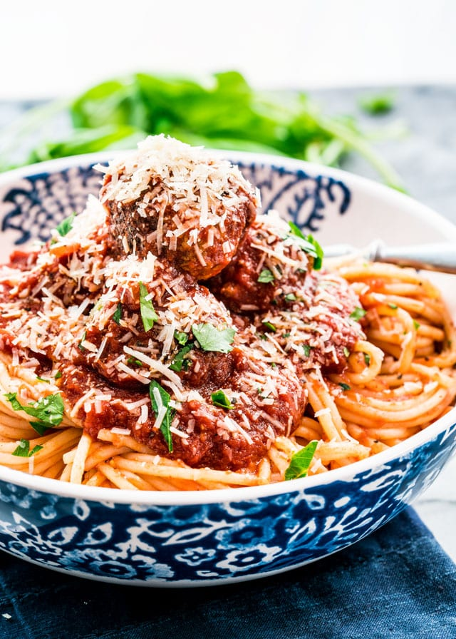 a bowl full of spaghetti topped with meatballs, parmesan, and parsley