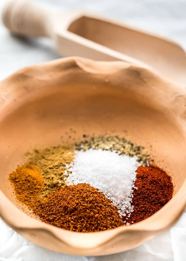 a bowl with salt, pepper, paprika, cumin, chili powder, and cayenne pepper.