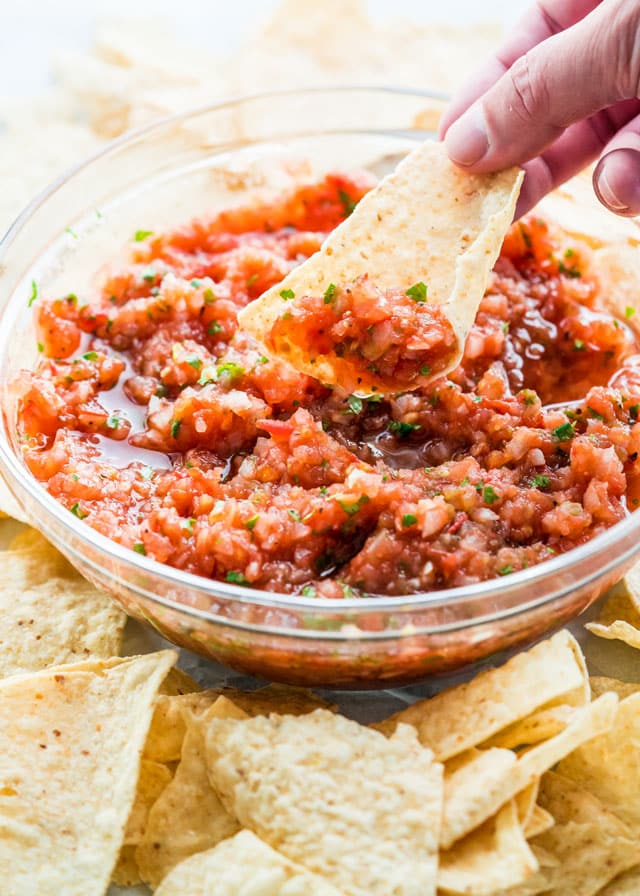 Homemade Salsa in a bowl surrounds by tortilla chips