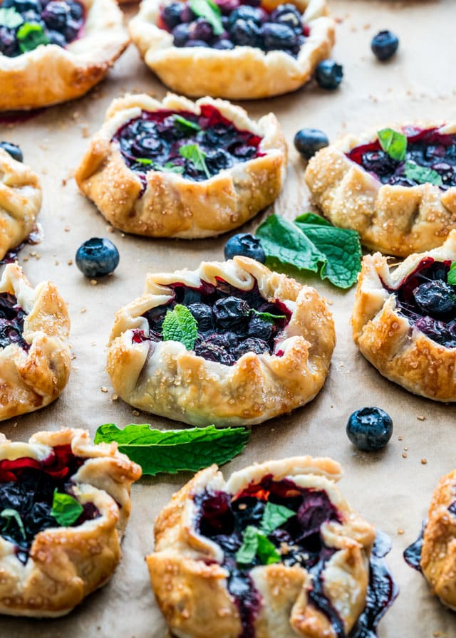 blueberry galettes on a baking sheet with fresh mint