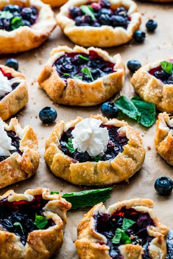 side view shot of mini blueberry galettes, 3 are topped with a dollop of whipped cream