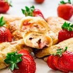 side view shot of strawberry cheesecake crescent rolls on a plate, one ripped in half exposing the center
