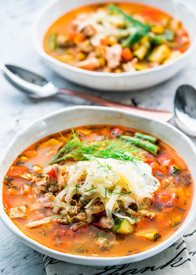 a bowl with soup filled with vegetables, chicken, and topped with cheese.