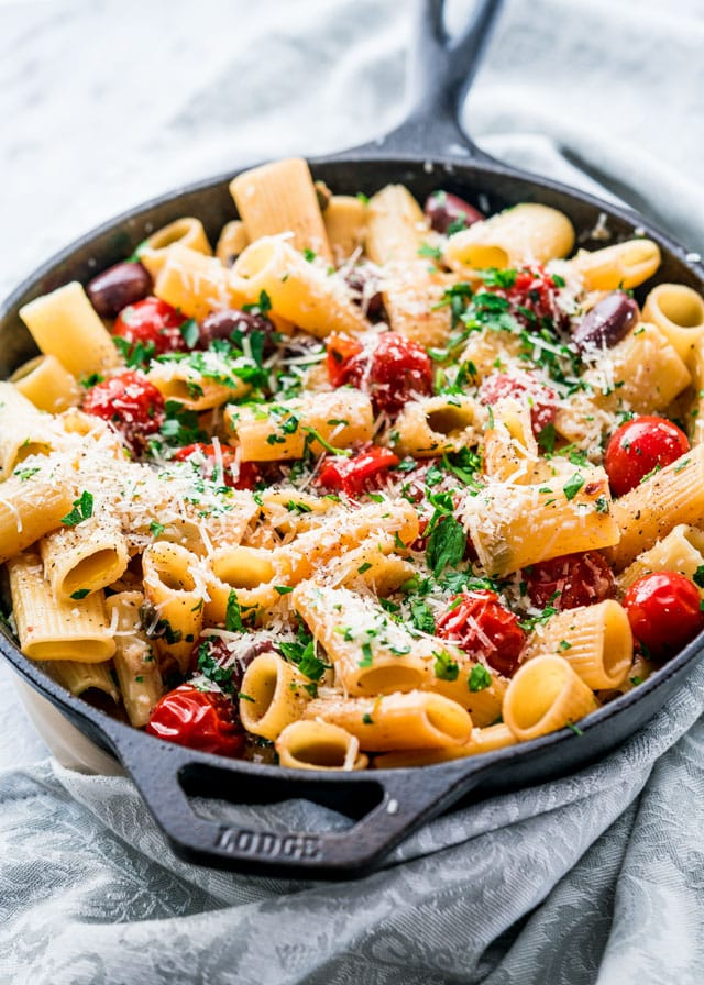 puttanesca in a skillet with parmesan, parsley, cherry tomatoes, and olives
