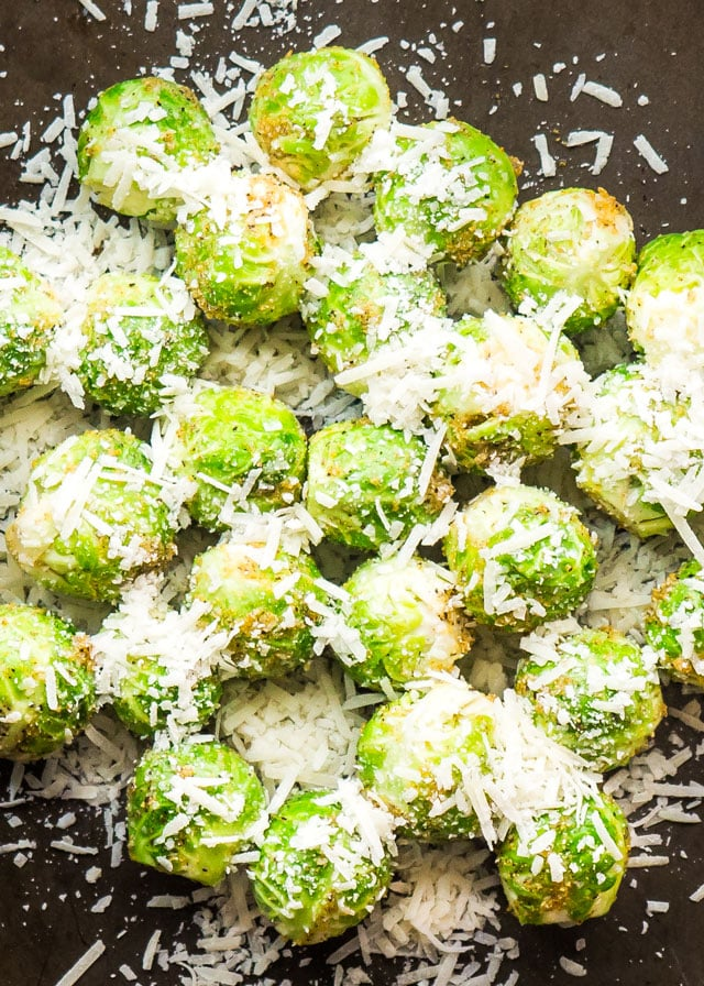 brussels sprouts on a baking sheet topped with parmesan cheese