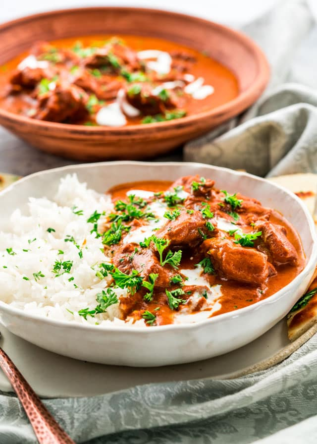 two plates with butter chicken and rice garnished with parsley