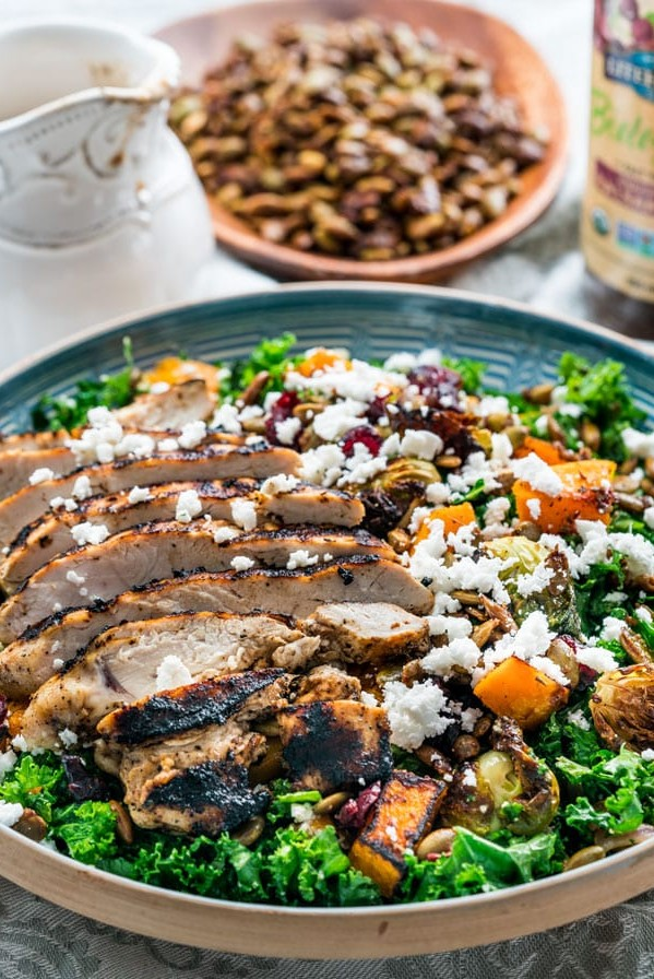 side view shot of the warm kale salad with roasted butternut squash, topped with sliced chicken breast and feta cheese