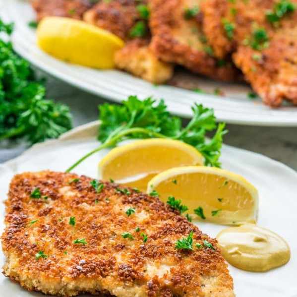 side view shot of a chicken schnitzel on a plate with mustard and lemon wedges
