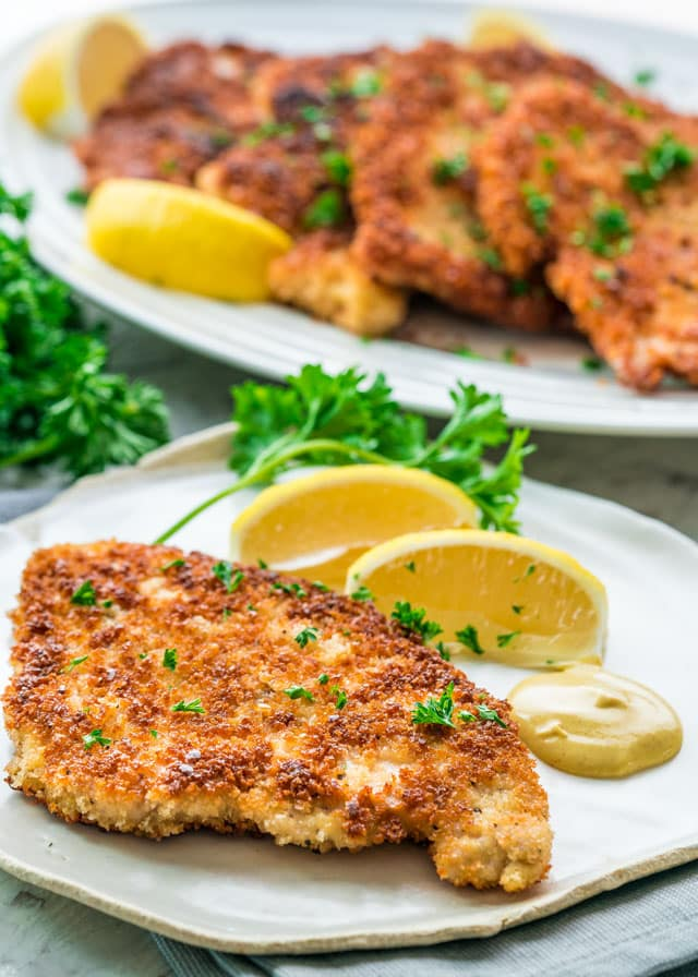 Chicken Schnitzel served on a plate with lemon wedges and mustard