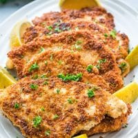 side view shot of chicken schnitzels on a serving plate garnished with lemon wedges