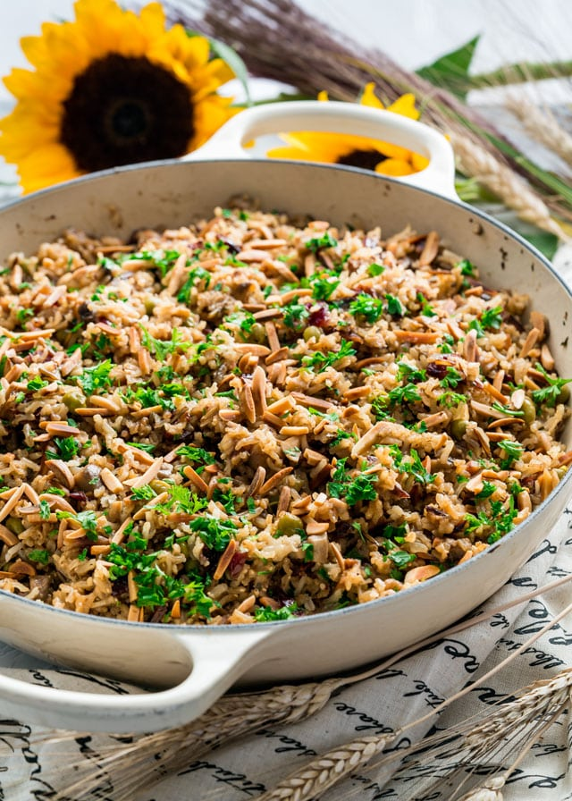 a pan full of harvest rice topped with toasted almonds and parsley