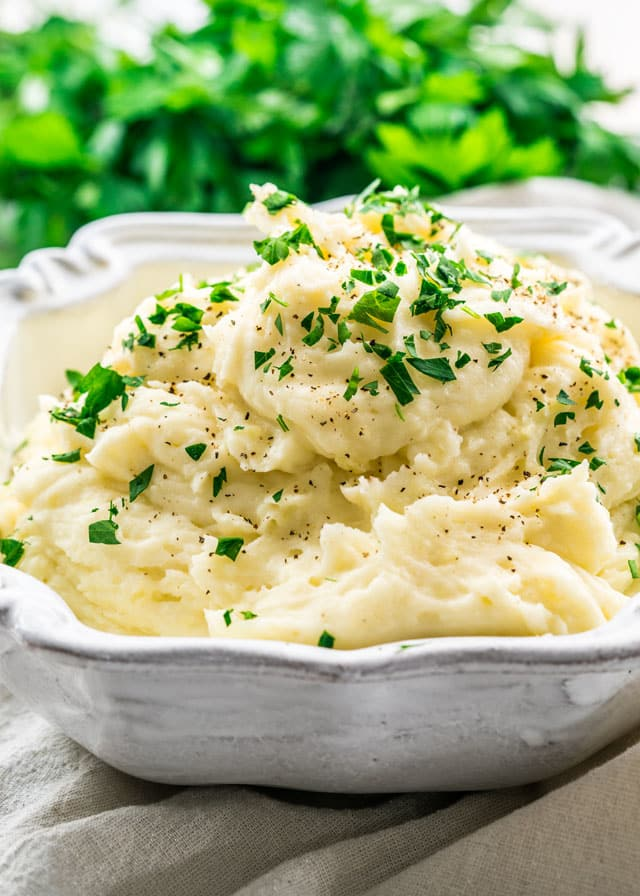 A serving bowl filled with Mashed Potatoes topped with pepper and parsley