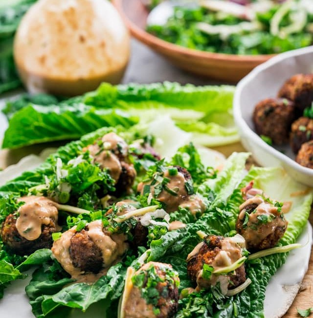 side view shot of three thai meatball lettuce wraps on a plate