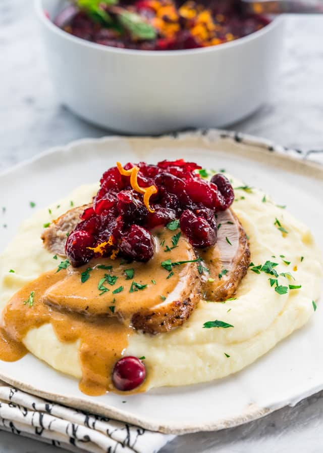 A plate of Instant Pot Turkey Breast on a bed of mashed potatoes topped with gravy and cranberries