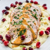 side view shot of sliced turkey breast drizzled with gravy atop a pile of mashed potatoes on a plate garnished with fresh cranberries