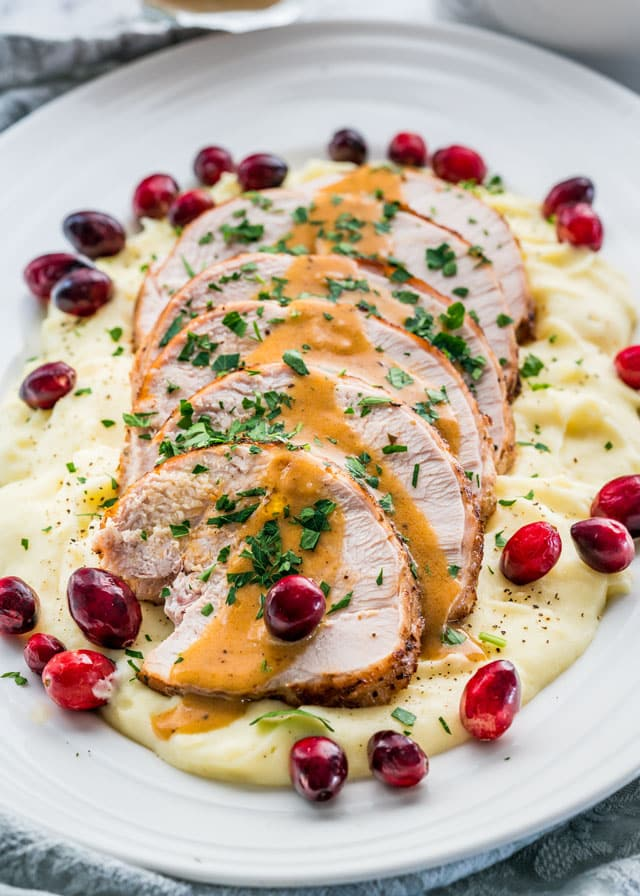 Instant Pot Turkey Breast sliced on a bed of mashed potatoes topped with gravy and cranberries