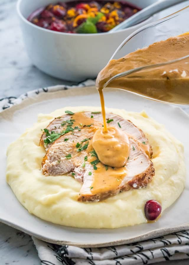 Pouring gravy over Instant Pot Turkey Breast and mashed potatoes
