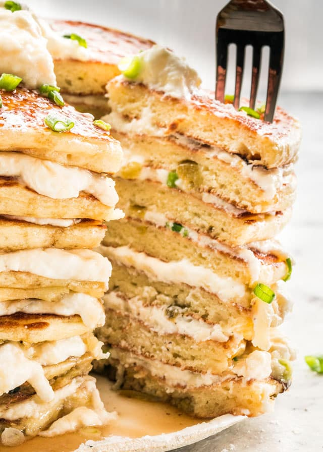 These Jalapeno Popper Pancakes are an incredible combination of sweet and savory. Extra moist pancakes with green chiles (that's right!) layered with a 3 cheese mixture and drizzled with maple syrup!