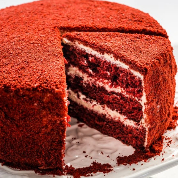 side view shot of a red velour cake with a slice missing and another slice cut