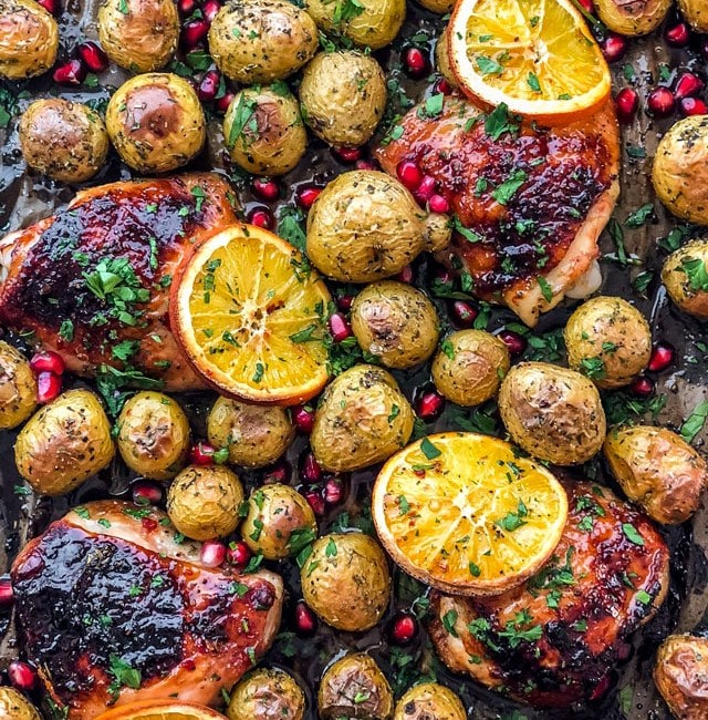 overhead shot of roasted honey orange chicken and potatoes topped with orange slices, pomegranate seeds and chopped parsley