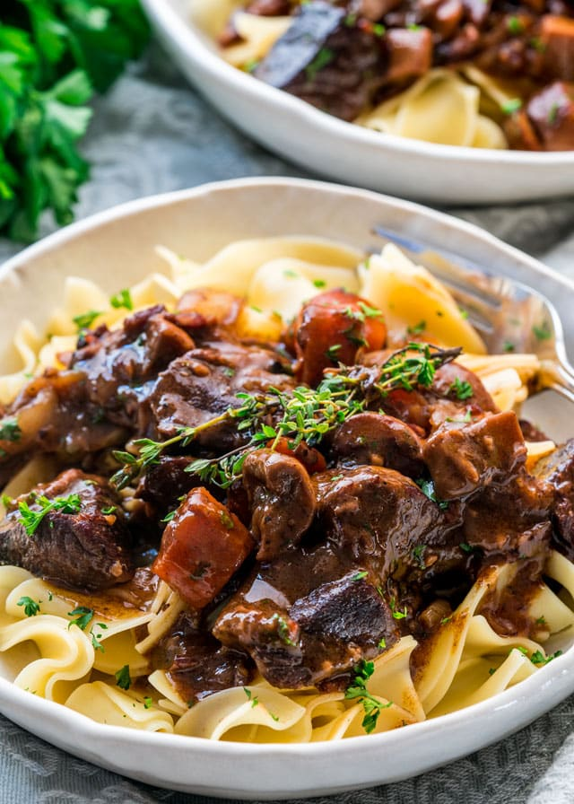beef bourguignon over noodles in a plate