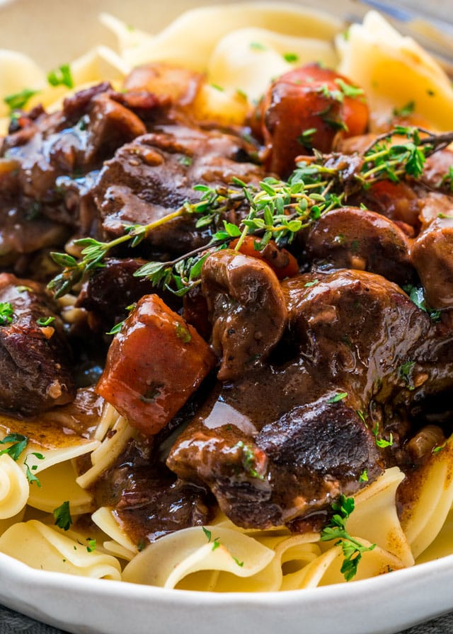 a closeup of beef bourguignon over noodles in a bowl