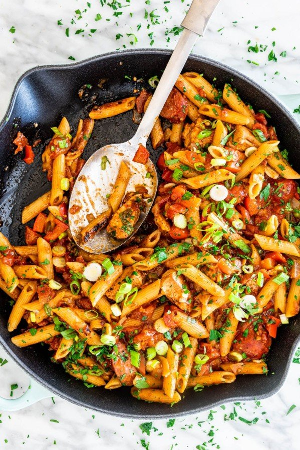 overhead shot of chicken jambalaya penne in a skillet with a serving spoon in it