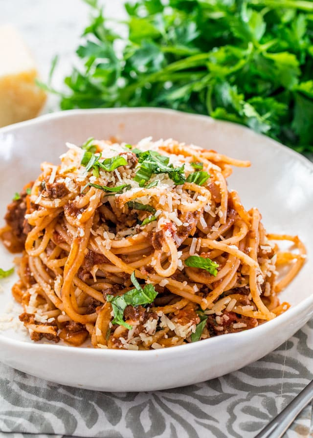 a bowl full of spaghetti bolognese with parsley in the background