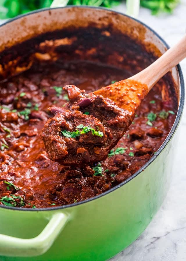 closeup of a big pot with beef chili and a spoon