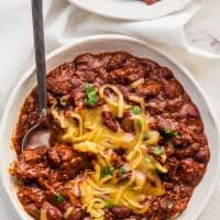 overhead shot of a bowl of chili topped with shredded cheddar cheese