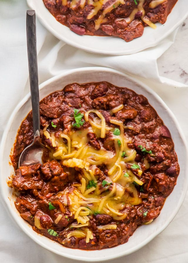 overhead of two bowls with chili and topped with cheese