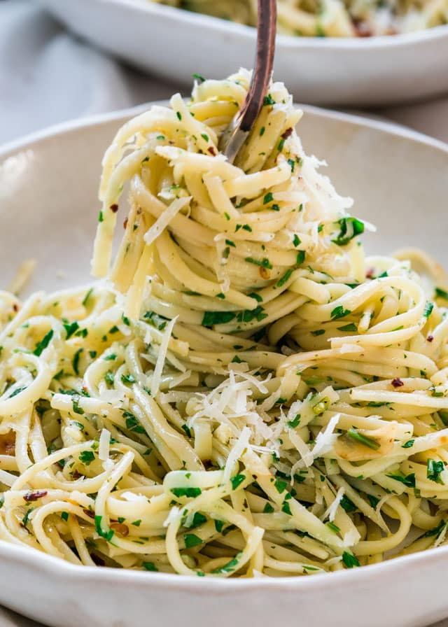Aglio e Olio in a plate with a fork twirling pasta