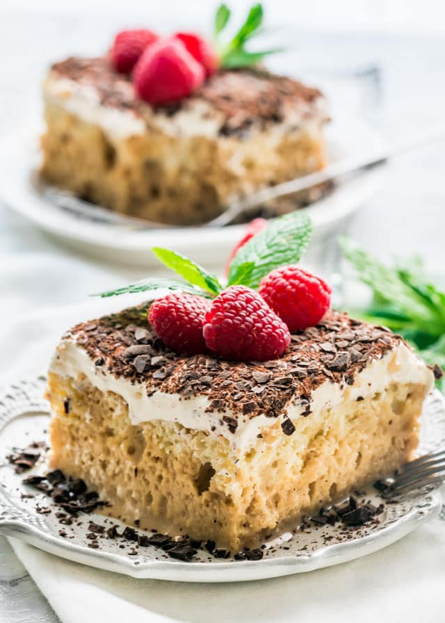 Tiramisu Tres Leches Cake slice on a white plate with raspberries and chocolate on top