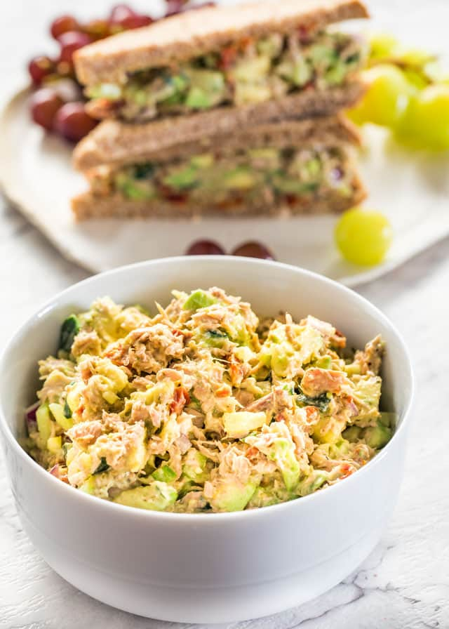 Avocado Tuna Salad in a bowl with a Avocado Tuna Salad sandwich on a plate in the background