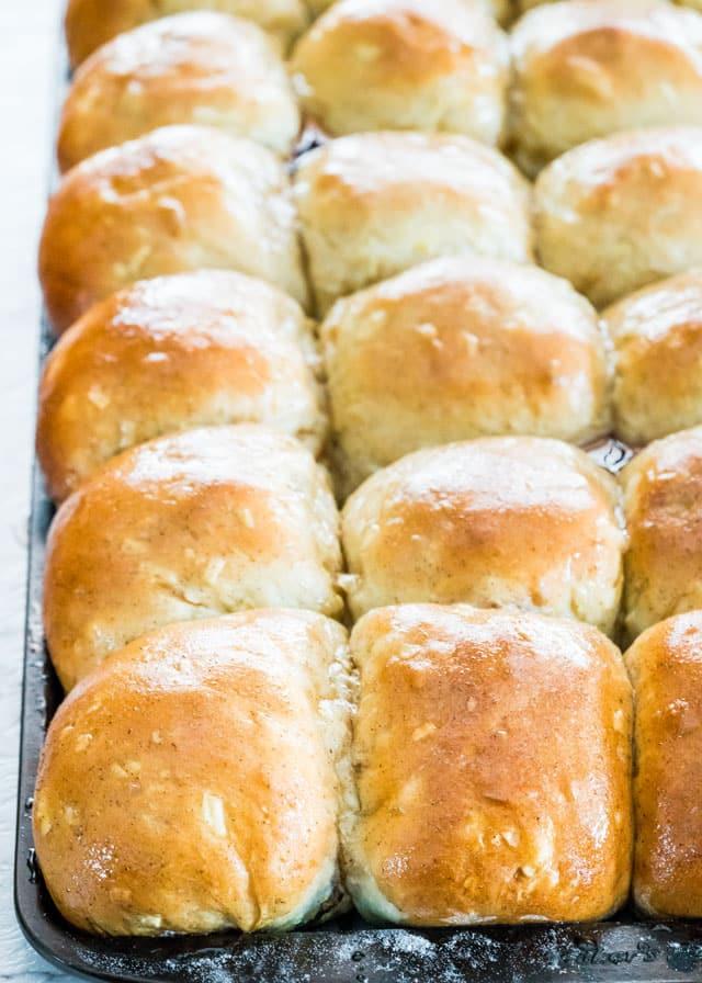 hot cross buns in a baking sheet with cinnamon sugar glaze