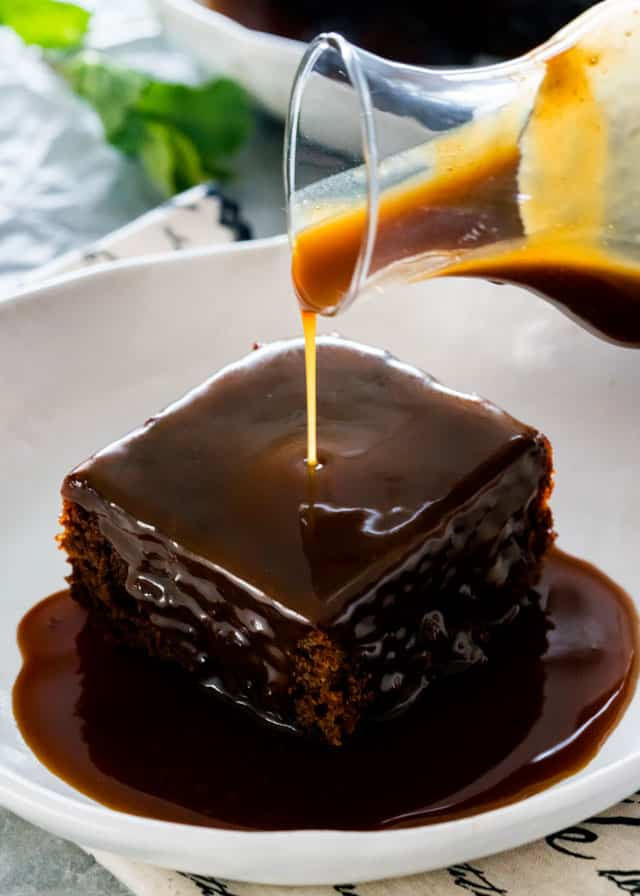 pouring sticky toffee sauce over a piece of date cake in a white plate