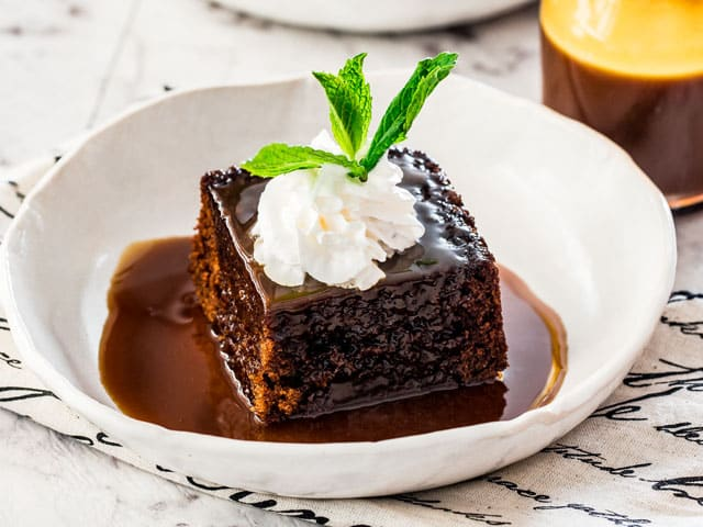 a piece of sticky toffee pudding in a white plate drenched with sticky toffee sauce and topped with whipped cream