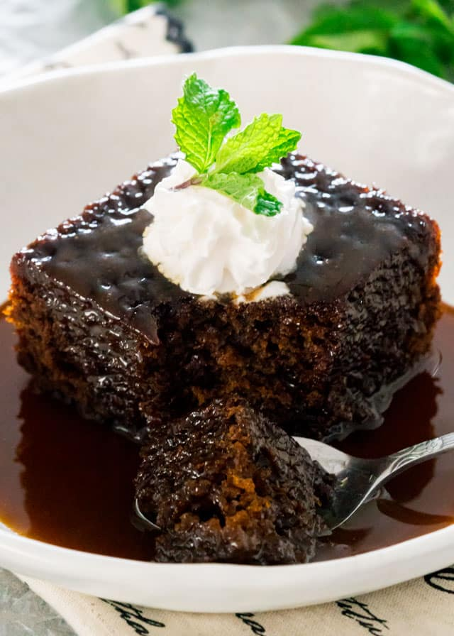 a piece of sticky toffee pudding with a spoon drenched with sticky toffee sauce and topped with whipped cream