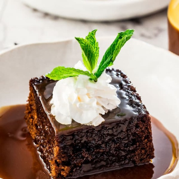 side view shot of a slice of sticky toffee pudding in a bowl topped with a dollop of whipped cream and a sprig of mint