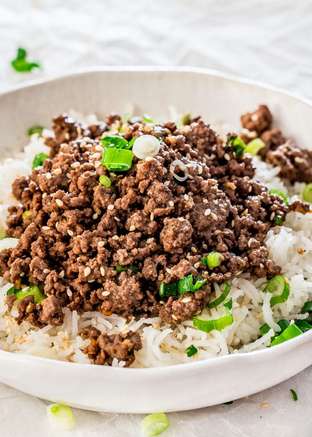 Korean Beef over rice in a white bowl garnished with sesame seeds and green onions over white rice
