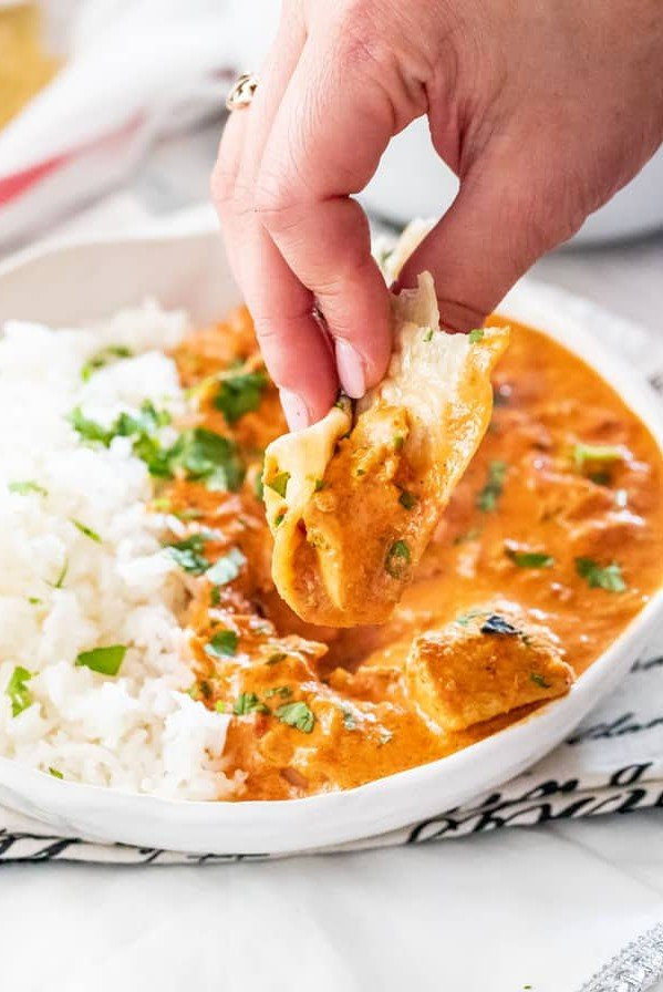 side view shot of a hand dipping a piece of naan bread into the bowl of chicken tikka masala