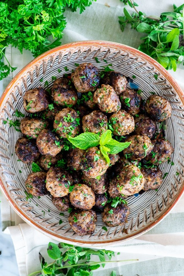 overhead shot of a bowl of greek meatballs surrounded by fresh herbs