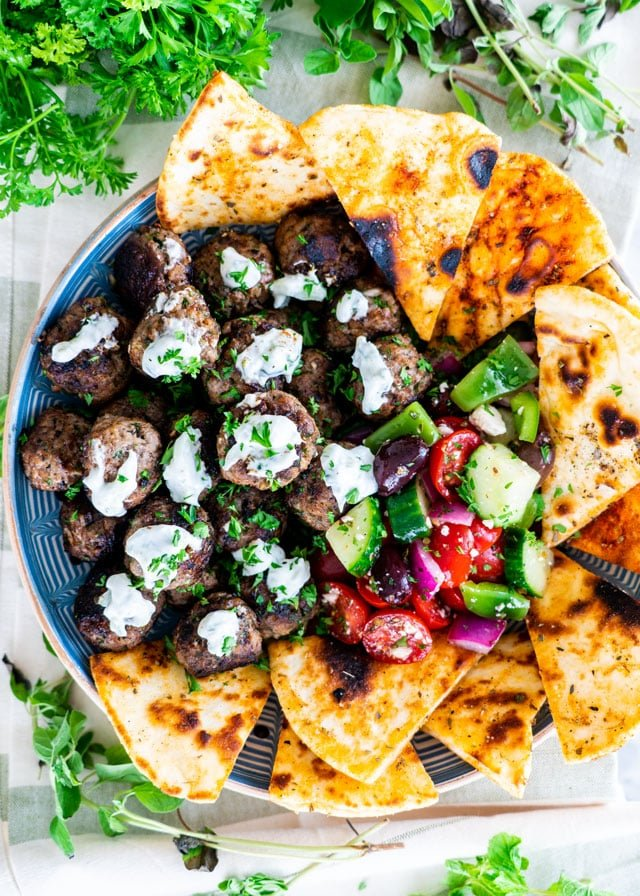 Greek Meatballs with tzatziki sauce, greek salad and pita chips on a platter
