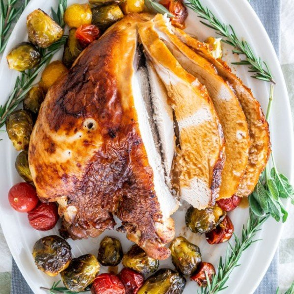 overhead shot of sliced brined roast turkey breast surrounded by roasted veggies and rosemary sprigs on a serving plate