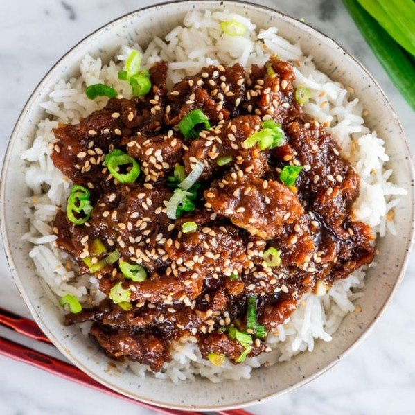overhead shot of a bowl of rice topped with instant pot mongolian beef