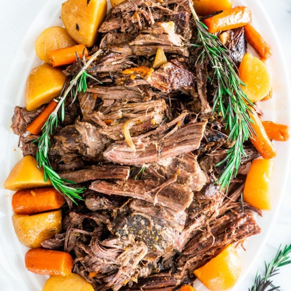 overhead shot of a crockpot roast on a large serving platter surrounded by potatoes and carrots